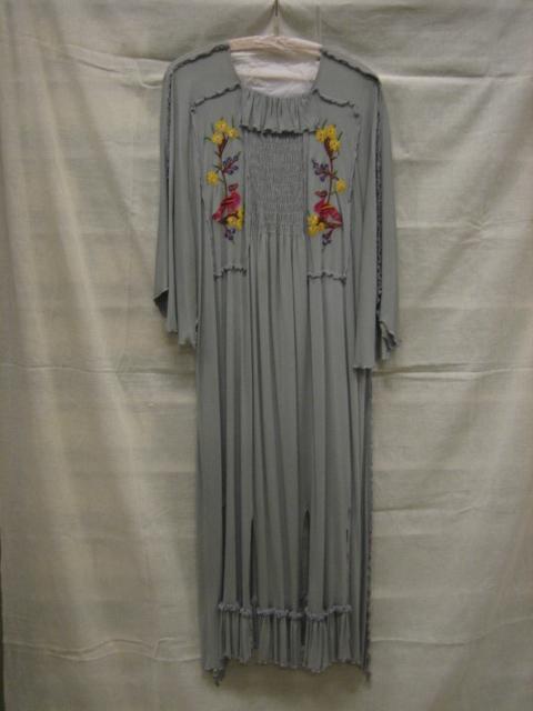 Jurk van grijze synthetische tricot met veelkeurig geappliqueerd borduursel van van vogels en bloemen en smockwerk op lijfje