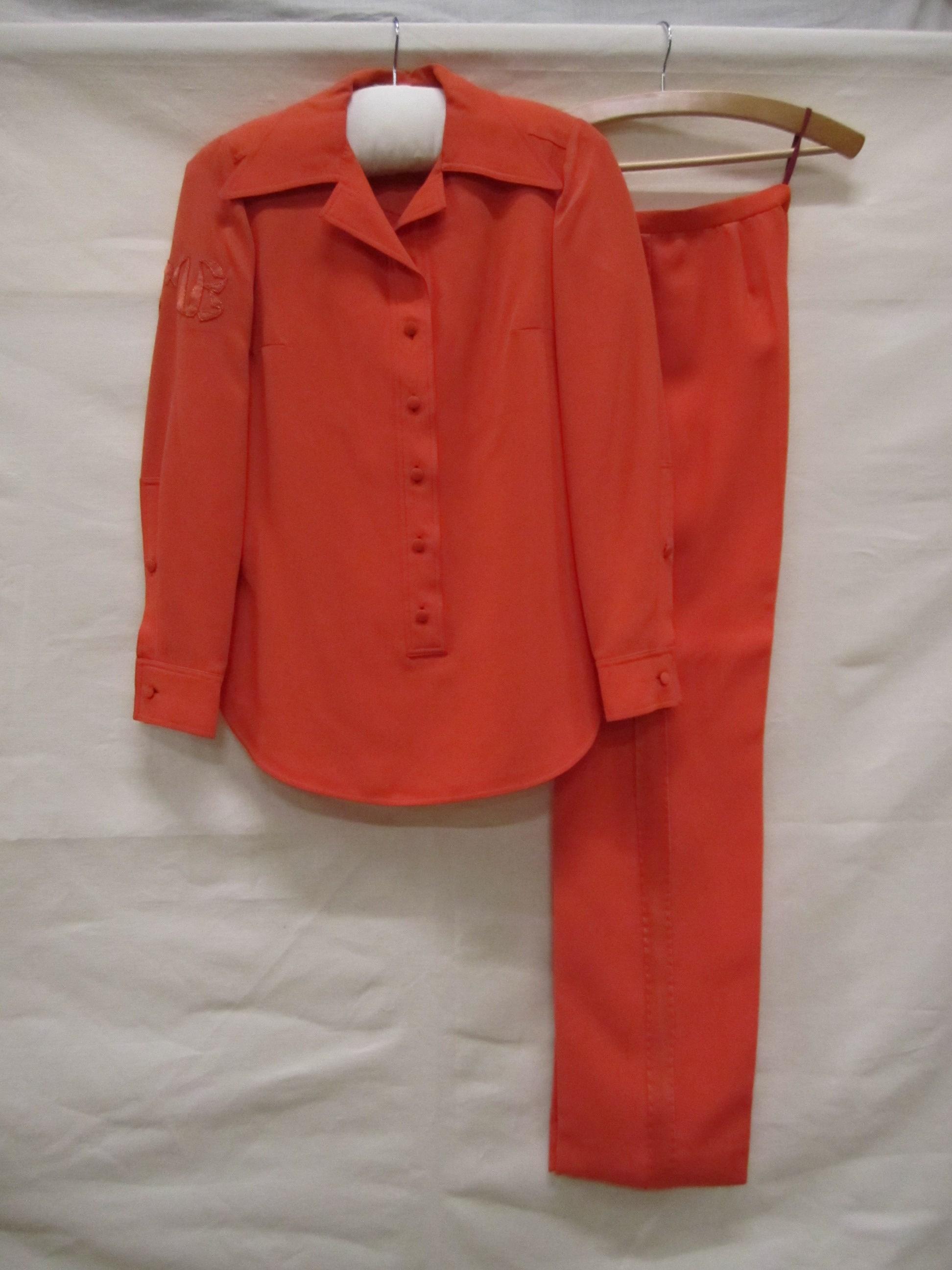 Broekpak van synthetische oranje crèpezijde, bestaande uit tuniek en lange broek
