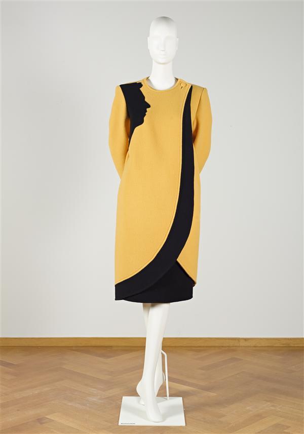 Ensemble bestaande uit jas van gele double face wol met applicatie in zwart en rok van zwarte wol met hoed van zwart wolvelours